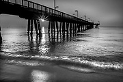 Limited Edition: Sunrise at Pompano Pier in Black & White. The sun is coming up and casts shadows and a big highlight on the water.