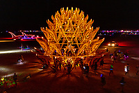 "The Temple of Awareness by: Utah Builders Community from: Salt Lake City, UT year: 2017<br /> <br /> Temples offer environments for us to immerse ourselves into an unworldly place of harmony and peace. The Temple of Awareness is an organic form, similar to a pine cone. Seen from above, it evokes aspects of a bloomed lotus. The Temple is a 13-sided dome structure that is 35 ft. in diameter at the base. It has seven levels that reach 35 ft. high, each level with projecting decorative wings encircling it. From a distance, the wings create a feeling of lightness, while the dome as a whole conveys a rooted presence. Participants enter the Temple through one of thirteen sizable inverted ""V"" openings. Inside is a welcoming, vaulted, airy interior defined by a series of shrinking, concentric circles soaring overhead. The dome top is left uncovered to allow for the participant's connection with the cosmos. The open interior design incorporates hundreds of shelves lining every wall, as well as several freestanding sub-altars that provide many niches and ledges for objects of remembrance. URL: http://www.utahbuilderscommunity.com Contact: utahbuilderscommunity@gmail.com"