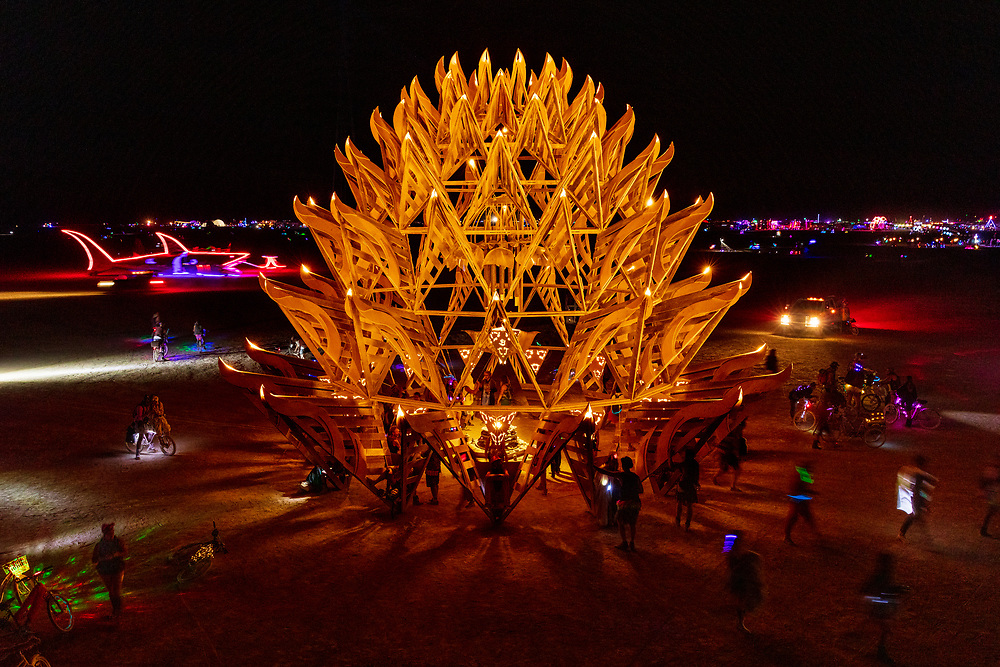 """The Temple of Awareness by: Utah Builders Community from: Salt Lake City, UT year: 2017<br /> <br /> Temples offer environments for us to immerse ourselves into an unworldly place of harmony and peace. The Temple of Awareness is an organic form, similar to a pine cone. Seen from above, it evokes aspects of a bloomed lotus. The Temple is a 13-sided dome structure that is 35 ft. in diameter at the base. It has seven levels that reach 35 ft. high, each level with projecting decorative wings encircling it. From a distance, the wings create a feeling of lightness, while the dome as a whole conveys a rooted presence. Participants enter the Temple through one of thirteen sizable inverted """"V"""" openings. Inside is a welcoming, vaulted, airy interior defined by a series of shrinking, concentric circles soaring overhead. The dome top is left uncovered to allow for the participant's connection with the cosmos. The open interior design incorporates hundreds of shelves lining every wall, as well as several freestanding sub-altars that provide many niches and ledges for objects of remembrance. URL: http://www.utahbuilderscommunity.com Contact: utahbuilderscommunity@gmail.com"""
