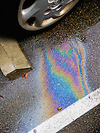 Rainbow colors of spilled oil on wet pavement next to a parked car. WATERMARKS WILL NOT APPEAR ON PRINTS OR LICENSED IMAGES.