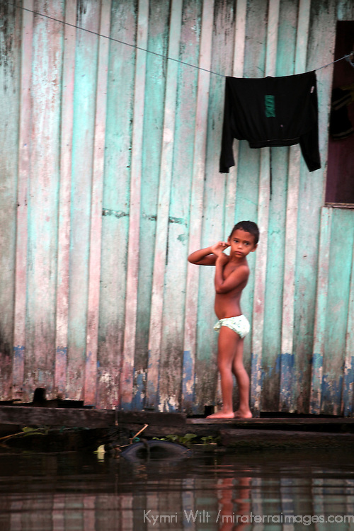 South America, Brazil, Amazon.  A young child stands outside house on river.