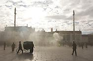 Pilgrims and merchants walk and pray in the juniper smoke on The Barkor at The Jokang Monastery, Lhasa, Tibet.