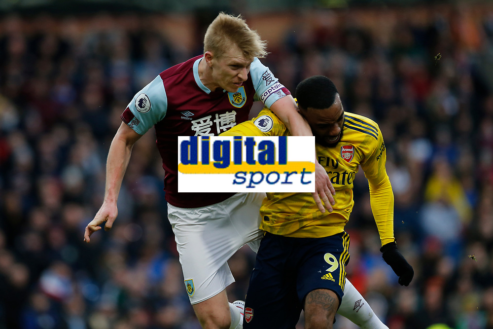 Football - 2019 / 2020 Premier League - Burnley vs. Arsenal<br /> <br /> Ben Mee of Burnley wins an aerial challenge against Alexandre Lacazette of Arsenal, at Turf Moor.<br /> <br /> <br /> COLORSPORT/ALAN MARTIN