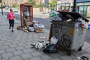 A jogging lady runs past a controversial local issue of discarded rubbish and fly-tipped litter on the street, on 7th March 2017, in Herne Hill, SE24, London borough of Lambeth, England.