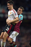 Mark Noble of West Ham United lifts Ander Herrera of Manchester United off the pitch for time wasting as Herrera had to leave the field injured.. The Emirates FA cup, 6th round replay match, West Ham Utd v Manchester Utd at the Boleyn Ground, Upton Park  in London on Wednesday 13th April 2016.<br /> pic by John Patrick Fletcher, Andrew Orchard sports photography.