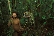 A Kombai man, with a rat tail headband around his forehead, holds up an arrow with a pierced but still live lizard in Papua, Indonesia. September 2000. The lizard was shot down from a tree. The Kombai are a so-called treehouse people who build their homes high up in the trees.