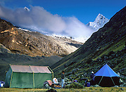 Alpamayo peak (19,500 feet elevation) soars above tents on the Santa Cruz Trek in Huascaran National Park, Cordillera Blanca, Andes Mountains, Peru, South America. UNESCO honored Huascaran National Park on the World Heritage List in 1985. The Cordillera Blanca mountain range is in the Sierra Central of the Peruvian Andes.