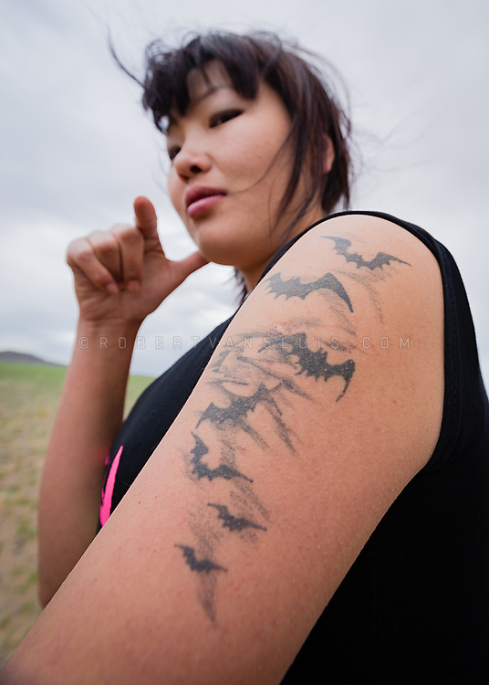 Close up portrait of a woman with bats tattooed on her arm. Photo © robertvansluis.com