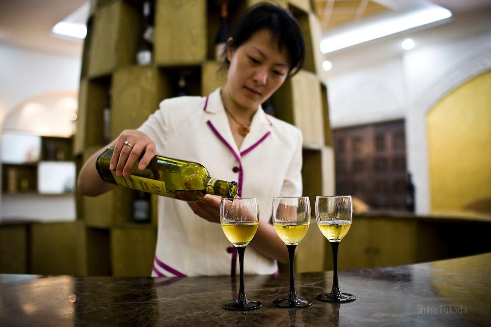 A winery worker serves Huadong Chardonnay at the Huadong Winery in Qingtao, China, June 23, 2009.