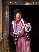 A Brokpa woman spins sheep wool using a drop spindle called a Yoekpa, Merak, Eastern Bhutan. The Brokpa, the semi-nomads of the villages of Merak and Sakteng are said to have migrated to Bhutan a few centuries ago from the Tshona region of Southern Tibet. Thriving on rearing yaks and sheep, the Brokpas have maintained many of their unique traditions and customs. Their distinctive hat known as tsipee cham is made of yak felt with long twisted tufts, said to keep the rain from running onto their faces.