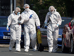 © Licensed to London News Pictures . 19/05/2014 . Huddersfield , UK . Police and forensic examiners at the scene on Reinwood Road , Huddersfield , where a woman has been stabbed to death and four children injured . A nine-year-old boy was also found outside the property with a stab wound to his arm and was treated in hospital. Another nine-year old boy, an 11-year-old boy and a six-month-old baby girl were also present and treated for minor injuries . Police say they have detained a 39 year old man at the scene . Photo credit : Joel Goodman/LNP