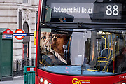 Seen reflected in the windscreen of a passing bus, a government NHS National Heath Service advert displays the face of a Covid patient, urging Londoners to stay at home and not to take risks or bend the rules during the third lockdown of the Coronavirus pandemic, at Piccadilly Circus in the capitals West End, on 3rd February 2021, in London, England.