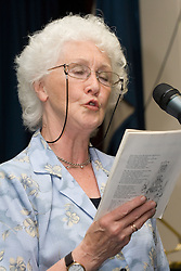 Elderly woman holding song sheet and singing into microphone,