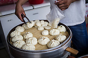 A Chinese street vendor sells typical bread called baozi on the streets of Yangshuo, Gulin, August 2, 2014.<br /> <br /> Food and games are a real pleasure for the life of Chinese community. <br /> At home, in the streets, at the park or in restaurants, the chance to find someone eating or playing is considerably high.<br /> <br /> © Giorgio Perottino