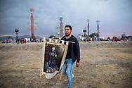07 marzo 2021, Tultepec, México. Un hombre lleva un estandarte de San Juan de Dios en los terrenos de quema de este municipio. Al fondo, castillos de torre instaladas para la celebración anual en honor a San Juan de Dios.