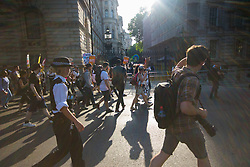 London, June 21st 2017. Protesters march through London from Sheherd's Bush Green in what the organisers call 'A Day Of Rage' in the wake of the Grenfell Tower fire disaster. The march is organised by the Movement for Justice By Any Means Necessary and coincides with the Queen's Speech at Parliament, the destination. PICTURED: Protesters cast long shadows on Whitehall as they arrive at Downing Street.