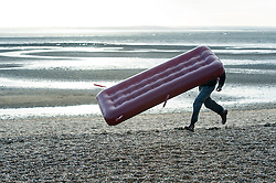 (c) Licensed to London News Pictures. 15/01/2015 Essex, UK.  One man brought an inflatable bed to the seafront in the freezing wind blowing along the Thames Estuary at Southend on Sea. Unfortunately the wind gusted and tore it out of his hands. He stated he was going take it into the sea to float. Fortunately it was low tide. Photo credit Simon Ford/LNP