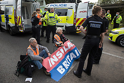 Godstone, UK. 13th September, 2021. Surrey Police officers arrest Insulate Britain climate activists who had blocked a slip road from the M25 as part of a new campaign intended to push the UK government to make significant legislative change to start lowering emissions. The activists, who wrote to Prime Minister Boris Johnson on 13th August, are demanding that the government immediately promises both to fully fund and ensure the insulation of all social housing in Britain by 2025 and to produce within four months a legally binding national plan to fully fund and ensure the full low-energy and low-carbon whole-house retrofit, with no externalised costs, of all homes in Britain by 2030 as part of a just transition to full decarbonisation of all parts of society and the economy.