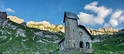 """At Meglisalp is a 1904 mountain chapel (Kapelle Maria zum Schnee, """"Holy Mother Mary of the Snow""""). Berggasthaus Meglisalp can only be reached on foot in the heart of the Alpstein mountain chain in the Appenzell Alps, Switzerland, Europe. This authentic mountain hostelry, owned by the same family for five generations, dates from 1897. Meglisalp is a working family dairy farm. This image was stitched from multiple overlapping photos."""