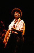 Joan Armatrading playing guitar and looking up