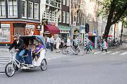 In Amsterdam rijden toeristen mee met een fietstaxi door de binnenstad. <br /> <br /> Amsterdam tourists ride with a bicycle cab through the city.