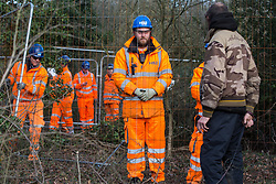 Harefield, UK. 7 February, 2020. An activist observes HS2 engineers erecting Heras fencing to surround three environmental activists from Extinction Rebellion who have climbed a veteran oak tree close to the Harvil Road wildlife protection camp in order to try to protect it from felling. HS2 are expected to try to fell large numbers of mature trees in the immediate vicinity over the weekend even though the high-speed rail link is still awaiting Boris Johnson's approval.