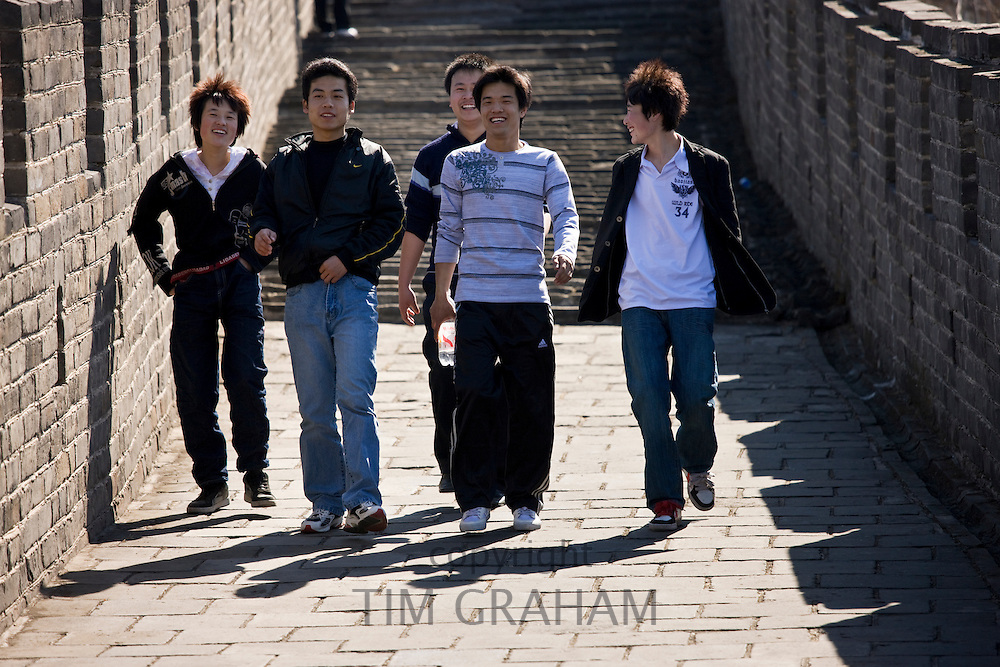 Chinese youths walk the ancient Great Wall of China at Mutianyu, north of Beijing, China