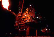 Alaska. Cook Inlet. Gas flare illuminates the Dolly Varden oil production platform oil rig at night.