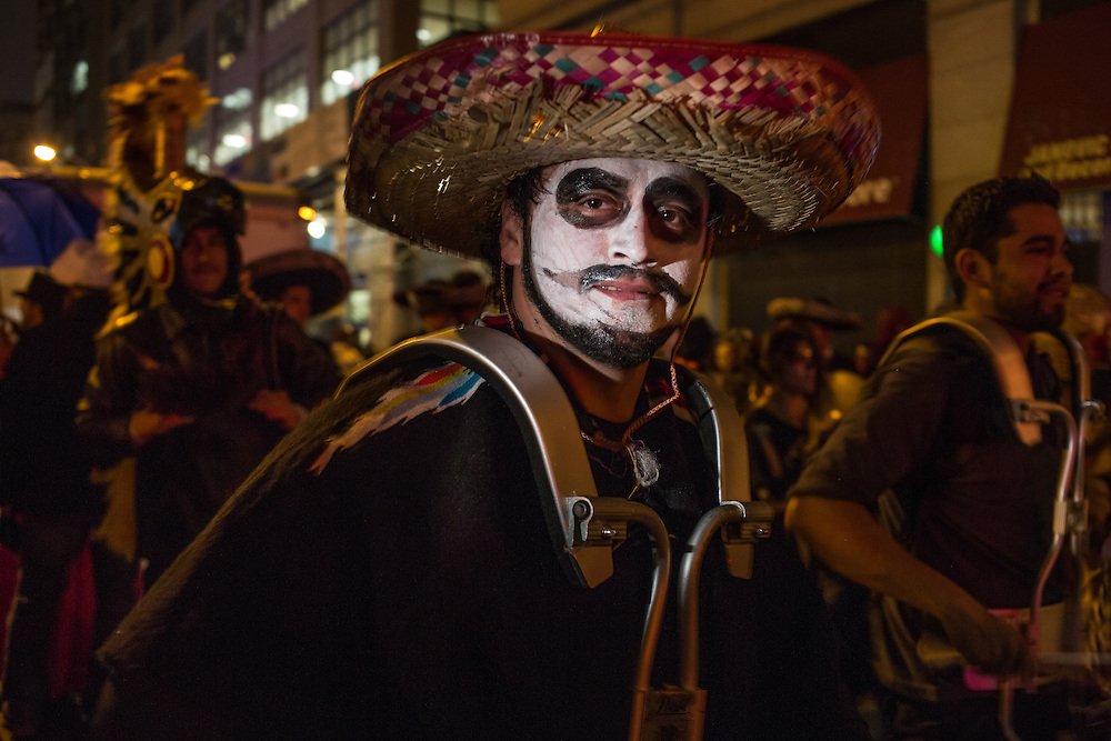 New York, NY, October 31, 2013. A drummer wearing  a Mexican sombrero and white facepaint in New York's Greenwich Village Halloween Parade.