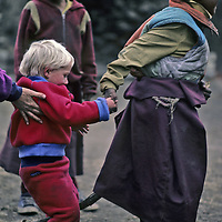 NEPAL, Himalaya. Ben Wiltsie, age 3 plays with young Sherpa monks at Tengboche Monastery, Khumbu Region. Mother (Meredith Wiltsie) looks on.