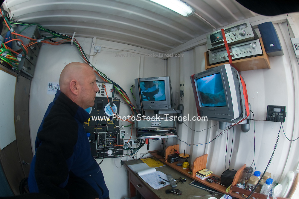 Commercial Diver communication and control. Cables from the surface supply electrical power for the lights and torch, and allow communication with the surface. Monitors allow the inspector to see a control underwater actions. Photographed of the shore of Hadera, Israel