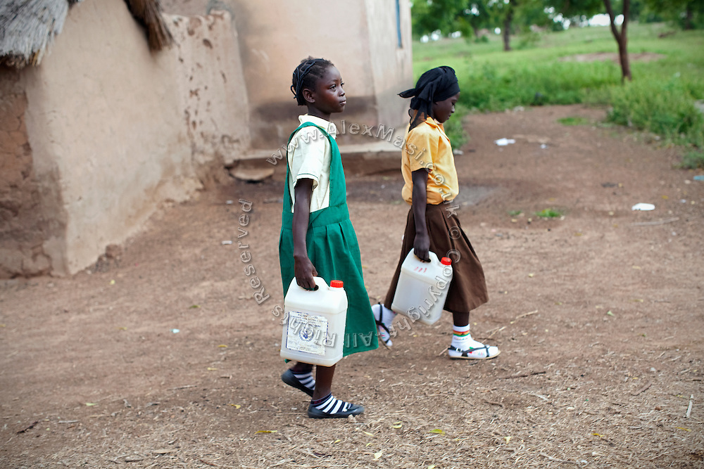 After having collected a load of Shea nuts each to help supporting their families, Hassana Ibrahim, 11, (left) and her classmate Rahima Ibrahim, 11, (right, not sisters) are walking back to their village with some water to bring along to their school in Boggu, Tamale, northern Ghana.