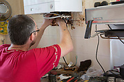 A Corgi registered plumber installing a new fuel efficient boiler onto a kitchen wall. Blackpool, Lancashire. United Kingdom
