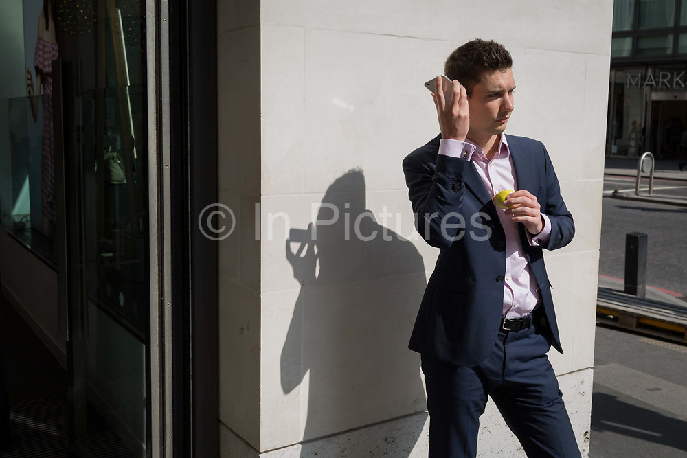 A young man listens to his phone in the City of London, the capitals financial district also known as the Square Mile, on 6th April 2017, in London, England.