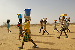 Children carry water for their teacher, Ouedraoga Madi in Zigberi, in a remote part of Burkina Faso in the desert region near the Malian border March 24, 2007. The village had no school and after years of waiting the parents decided to build their own school, desperate to get an education for their children.  Female education in Burkina Faso and West Africa is particularly difficult given the demands placed on the women and girls in society to do all of the household work like pounding the millet, preparing food, getting wood and water which is sparce and often kilometers away.  Ami Vitale