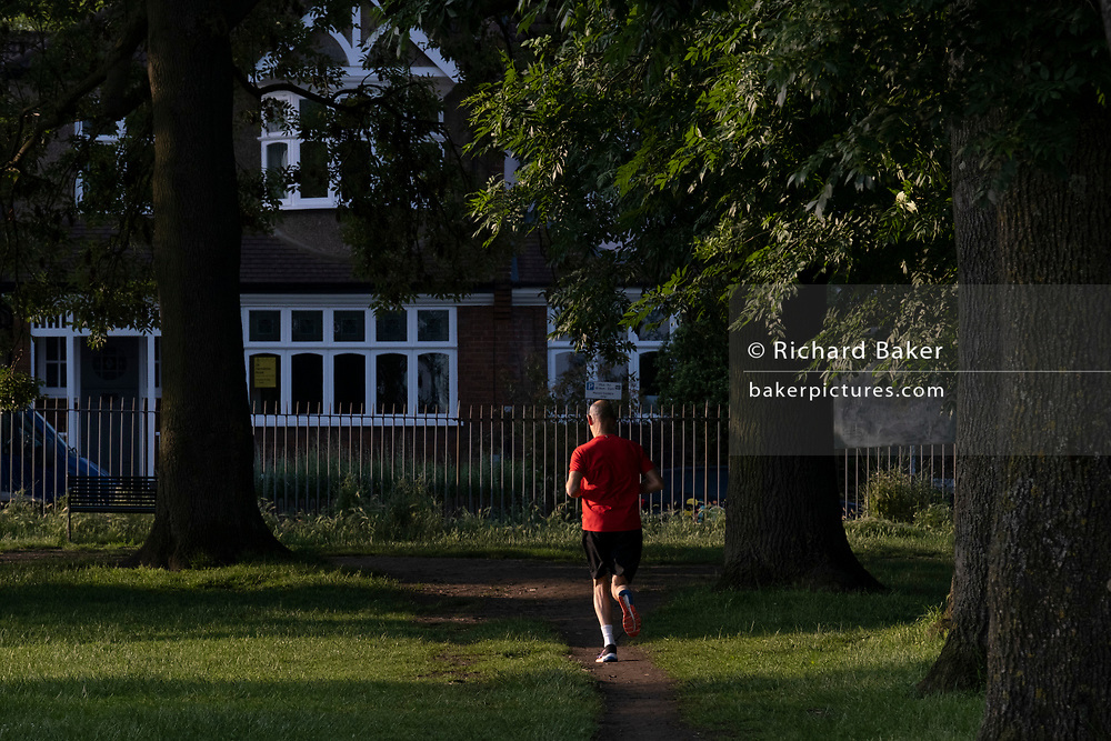 A runner wearing a red shirt jogs through early morning sunlight in Ruskin Park, a public green space in Lambeth, on 24th June 2021, in London, England. CREDIT RICHARD BAKER.