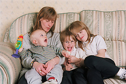 Single mother sitting on sofa with three young children,