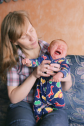 Mother holding crying newborn baby,