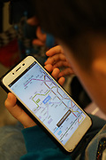 A child learning how to user maps and other usefuil programs whilst on the underground metro train. Shanghai