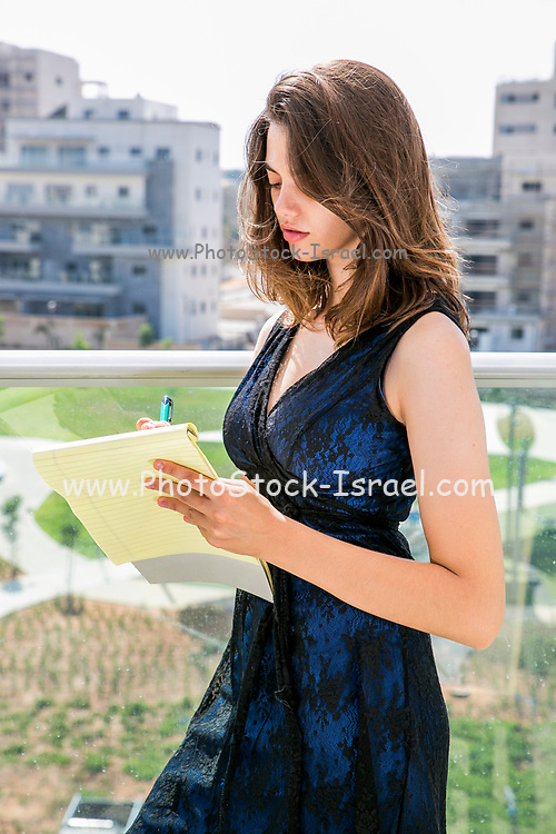 Young woman in formal dress takes notes on a yellow legal pad on the balcony of her home