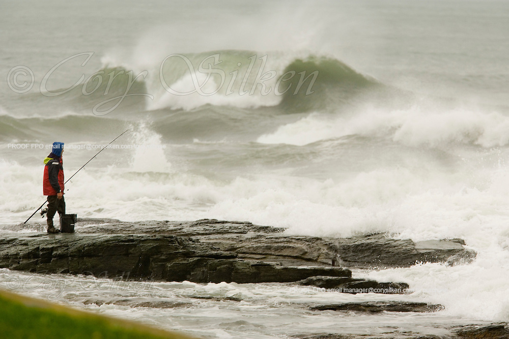 Fisherman standing out on the rocky beach with breaking waves.