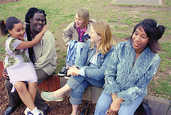 Group of single parents and child sitting on fence in playground,