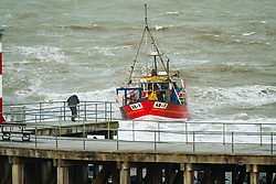 © Licensed to London News Pictures. 02/10/2017. Aberystwyth, Wales, UK.  A small fishing boat heads for the safety of the harbour, with gale force winds bringing huge waves crashing into the sea wall and lighthouse in Aberystwyth , as Storm Brian strikes the UK. Storm Brian, the second named storm of the season, is expected to bring disruptive rain and gale force winds to the west and north of the UK today.Yellow warnings for rain have ben issued by the Met Office. .Photo credit: Keith Morris/LNP