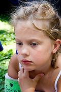 Sad girl age 7 with cast on broken arm. Svenskarnas Dag Swedish Heritage Day Minnehaha Park Minneapolis Minnesota USA