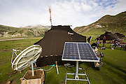 A solar panel and satellite dish are seen outside the handmade yak-wool tents Tibetan nomadic herders make their home in spring and summer in the Tibetan Plateau. The satellite dish was provided by China's central government; along with a solar battery charger, a truck battery, and a TV so the nomads can watch Chinese broadcasts and learn the Chinese language; an attempt, some say, to assimilate indigenous Tibetans.
