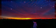 Stars at dawn, wintery with high red clouds and stars, a river in the foreground, textured.