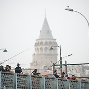 Fishermen line the Galata Bridge, with the Galata Tower in the background.