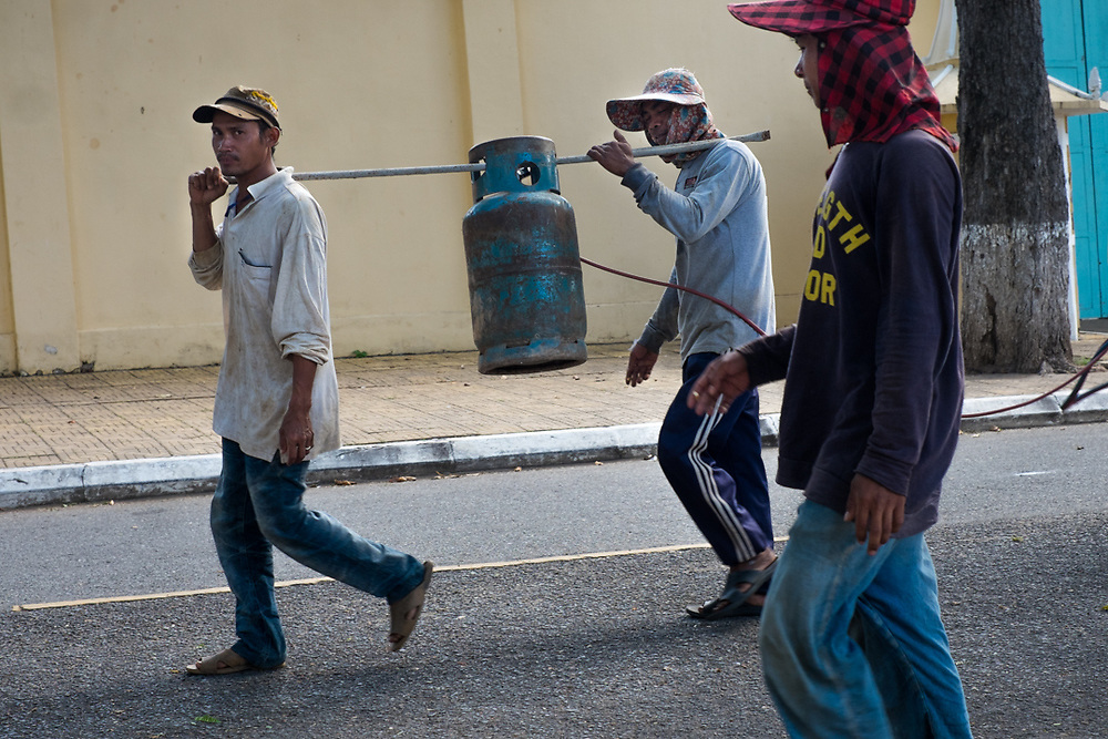 Workers transporting a gas bottle. Phnom Penh, Cambodia. <br /> Photo by Lorenz Berna
