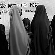 A young girl is seen among the women queued inside the food distribution point camp in Dagahaley refugee camp in the Dadaab, in northeastern Kenya. Hundreds of thousands of refugees are fleeing lands in Somalia due to severe drought and arriving in what has become the world's largest refugee camp. Photo: Sanjit Das/Panos