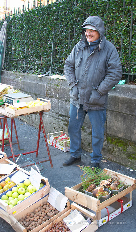Apples, hazelnuts, porcini cepe mushrooms for sale at a market stall at the market in Bergerac, a man dressed for winter freezing, selling. Bergerac Dordogne France